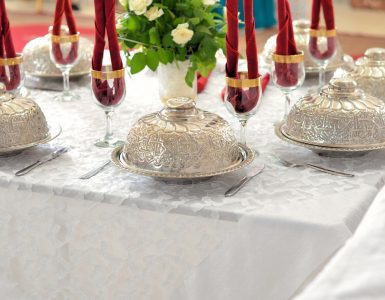 Ornate silver plate covers and stemmed glasses with folded cloth napkins are set on a table covered by white linen.