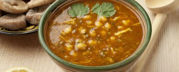 bowl of Moroccan harira soup in traditional bowl. Served with dates and dried figs.