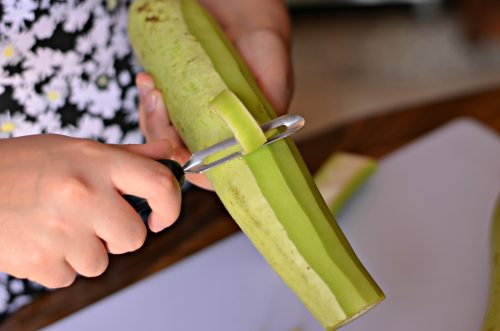 Image showing someone peeling a bottle gourd