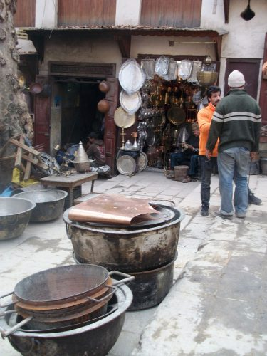 Two enormous cooking pots sit on a street in Seffarine located in old medina of Fez. The pots are used for making large batches of a preserved meat confit called khlii.