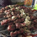 Several skewers of marinated and threaded cubes of meat and fat on a plate, waiting to be char grilled.