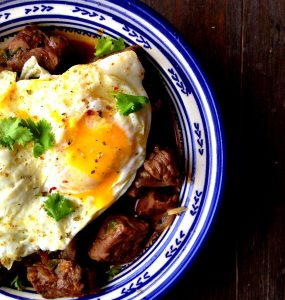 Kebab maghdour topped with fried eggs and served in a white tagine with blue patterns
