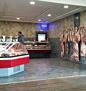 image of a Moroccan bucher shop. A customer is standing next to a glass-enclosed meat counter on the left and fresh whole meat is hanging to age on the right.