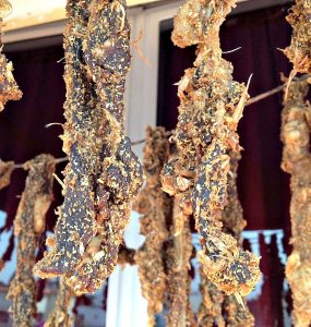 A photo of cured strips of meat hanging to dry on a line in order to make gueddid, a type of Moroccan dried meat.