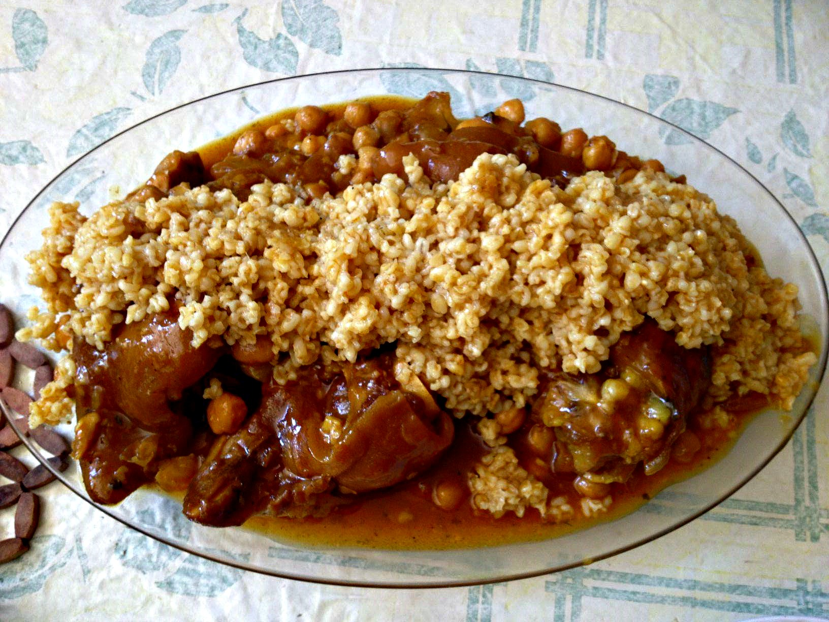 overhead image of a platter of Moroccan trotters and chickpeas topped by a garnish of wheat berries