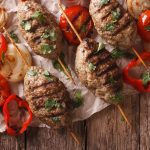 overhead image of kefta brochettes on wood table with grilled onions and tomatoes
