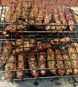 Photograph of grill basket full of kefta as the meat cooks over hot charcoal.