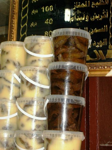 Plastic containers of khlii, a Moroccan confit of preserved meat, are stacked one on top of the other at a shop in Fes.