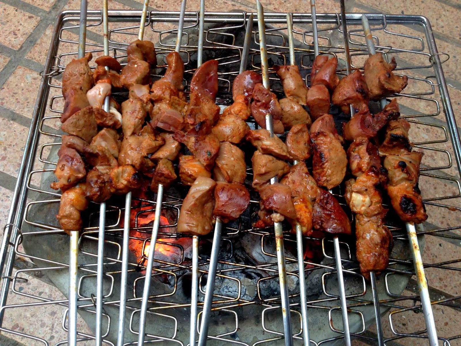 liver, heart and kidney brochettes cooking over charcoal