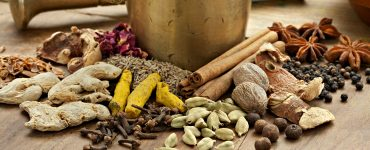 Image showing dry spices used to make ras el hanout at the base of a brass mortar and pestle.