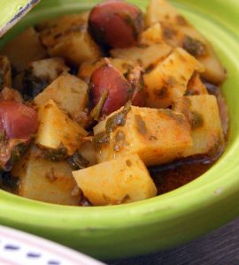 Moroccan potato salad with chermoula. The potatoes are cut in cubes and coated with chermoula, served in a green plate and decorated with purple olives