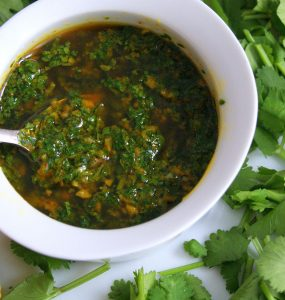 Chermoula marinade in a white bowl, topped with olive oil and surrounded by coriander leaves. A lemon appears in the corner.