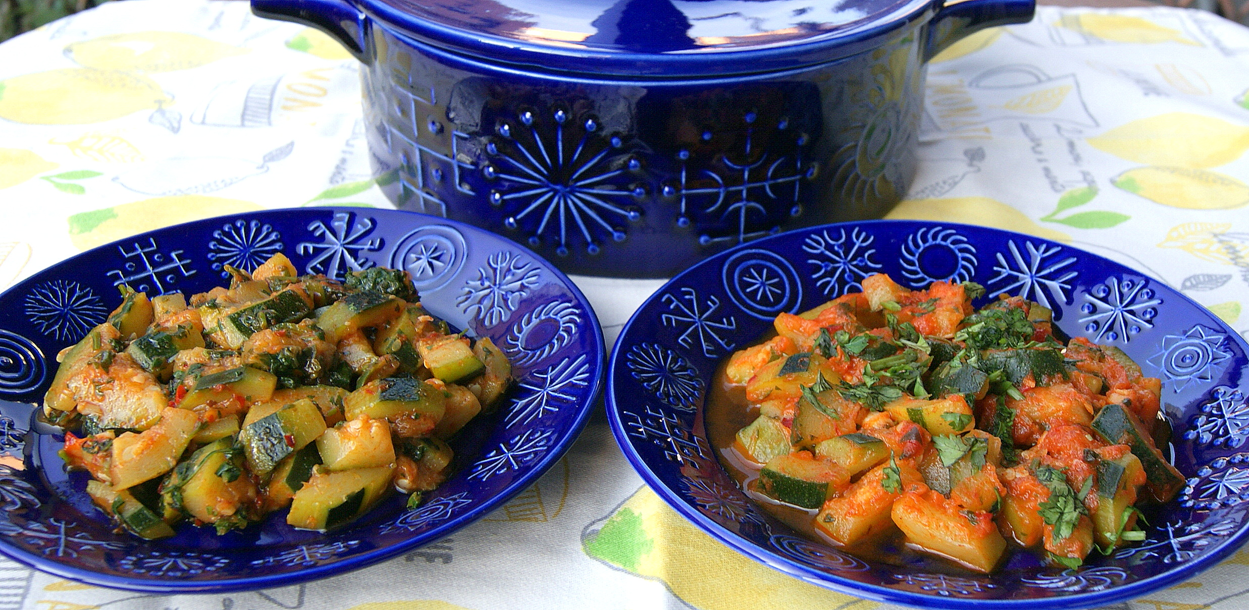 Two variations of chopped, cooked zucchini smothered with herbs and spices are shown side-by-side on decorated blue dishes.