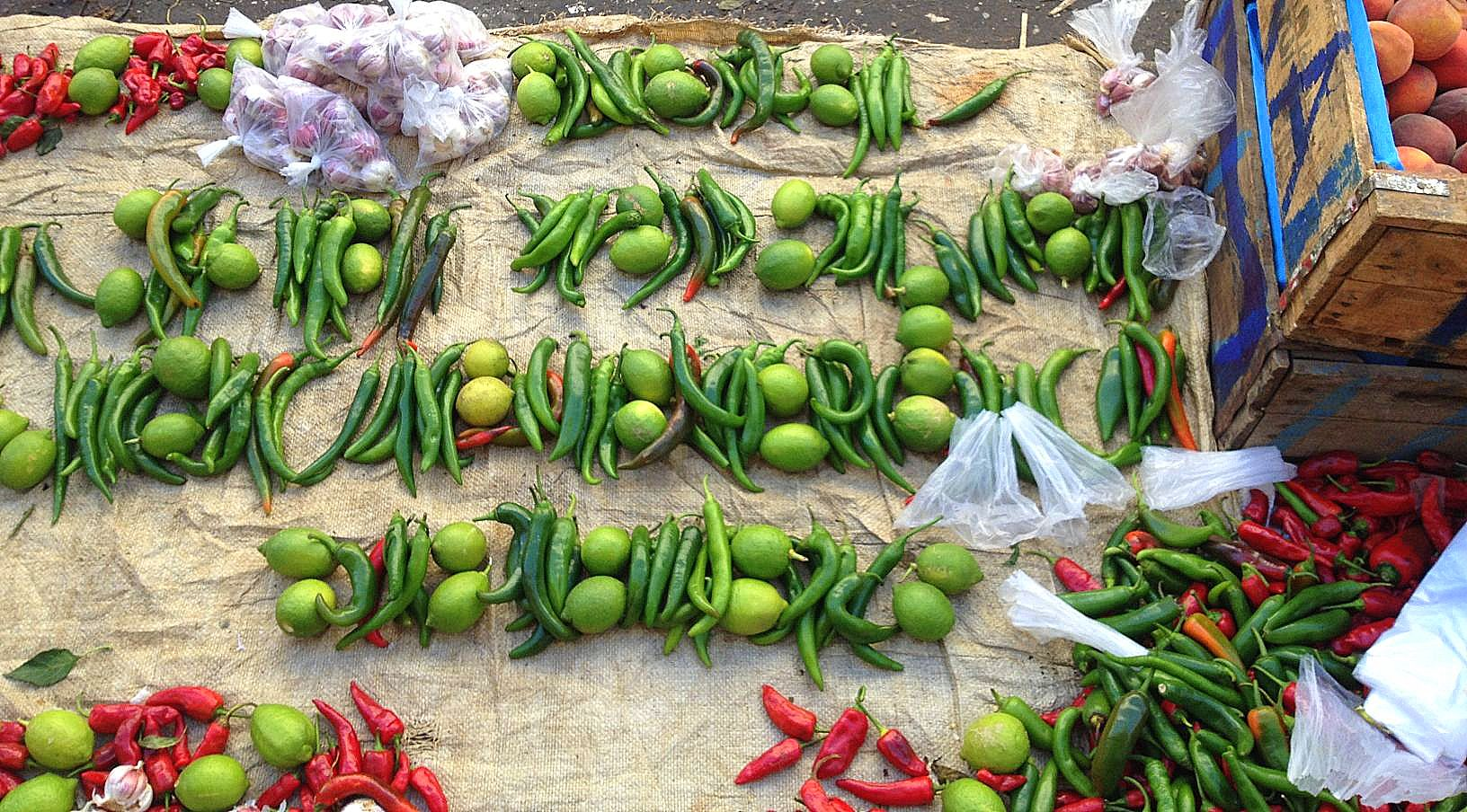 A spread of red and green chili , lime and garlic sold in the market., ideal for harissa