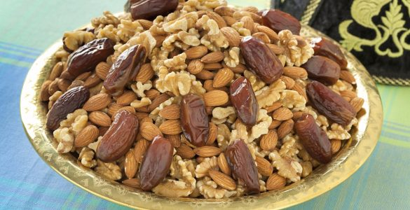 Walnuts, almonds and dates are mounded into a Moroccan serving dish. This assortment is a traditional food item to serve on Ashura.