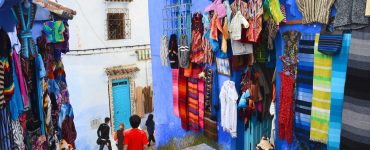 A narrow street in Chefchaouen, Morocco. Walls on either side are painted bright blue. Clothing and other items for sale are displayed outside.