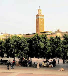 Image of garden square in Essaouira, Morocco. A mosque is in the background and people are walking and milling about, but the perspective is too far away to make out faces.