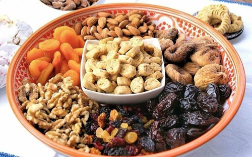 A plate with alternating piles of dried fruits and nuts around a bowl of nibble size cookies.