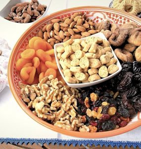 A large decorated serving platter features a bowl of krichlate, miniature shortbread cookies surrounded by almonds, walnuts, dried figs, dried apricots, dates and raisins.