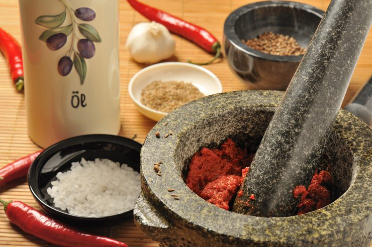 Close-up view of a mortar and pestle alongside chili peppers, coarse salt and spices. Harissa chili paste can be seen in the mortar.