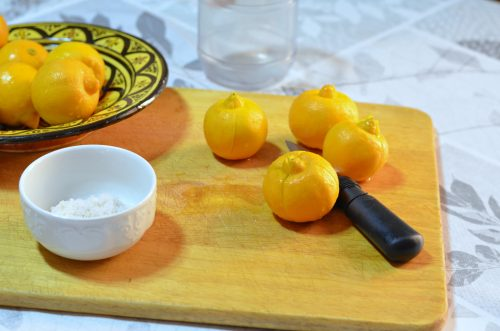 A large wooden cutting board sits beneath a decorated plate full of lemons. Some of the lemons are directly on the cutting board. Next to them are a knife and a bowl of coarse salt.