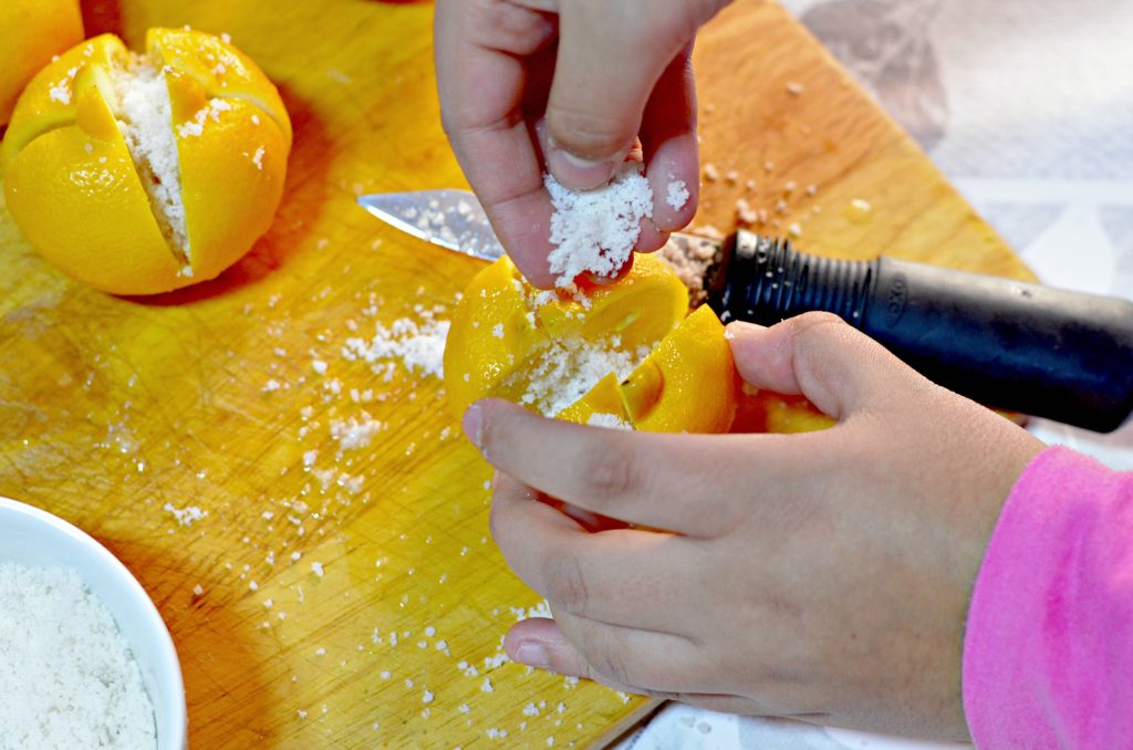 A close-up photo of hands and a lemon on a cutting board as someone adds salt to the lemon to make preserved lemons.