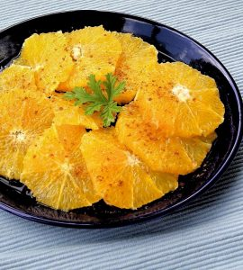 Round orange slices are arranged in overlapping fashion on a deep blue plate. The oranges are garnished with ground cinnamon.