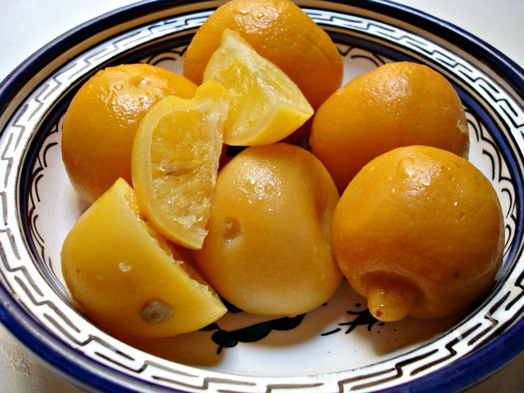 Whole preserved lemons and wedges of preserved lemon in a decorated ceramic dish.