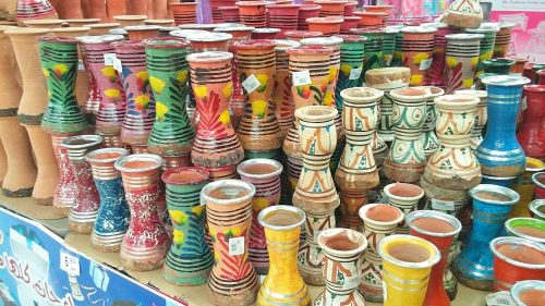 Small ceramic Moroccan drums, painted in colorful designs, are displayed for sale on a table.