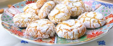 Moroccan almond ghrieba or macaroon on a plate. The cookies are chewy in texture with cracks on the surface. They are dusted with powdered sugar.