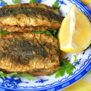 Moroccan coupled and fried sardines served over parsley leaves and served with lemon wedges