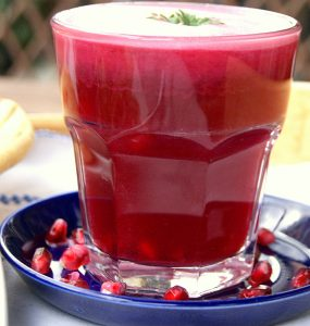 Moroccan pomegranate juice in a glass. The glass is on a small blue saucer and is surrounded by pomegranate seeds