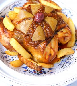 Moroccan chicken m'hammar topped with onion sauce, preserved lemons, purple olive and fried potatoes