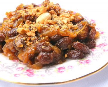 A close up photo of t'faya, a sweet confit of onions and raisin, topped with crushed almonds.