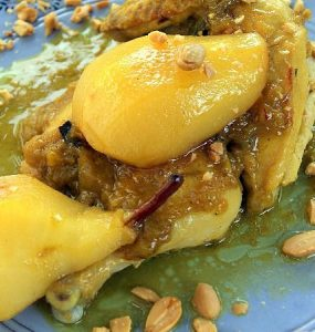 A serving of Moroccan chicken and caramelized pears garnished with fried almonds.