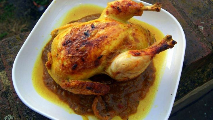 A whole chicken prepared m'qualli style sits on a plate surrounded by rich onion sauce which has separated from the oil. The chicken's skin is visibly roasted from a final stage of cooking in the oven.