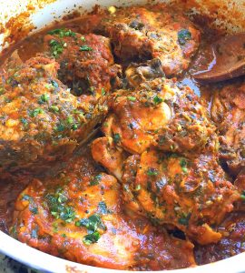 Cooked fish is shown in a skillet, covered in a Moroccan tomato- and chermoula-based sauce.