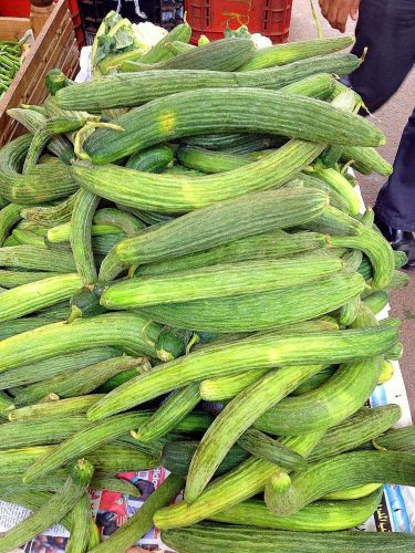 A pile of bendy cucumber in a market
