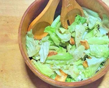 Overhead view of a wooden salad bowl filled with Caesar salad: crisp green romain lettuce topped with homemade croutons and shaved Parmesan cheese. Large wooden salad spoon and fork are resting in the bowl.