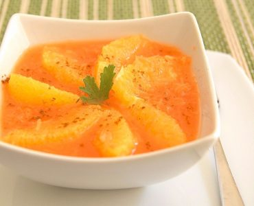 A white bowl holding Moroccan carrot and orange salad. Wedges of orange are arranged in a pinwheel as a garnish.