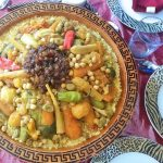 Overhead view of gorgeous presentation of Moroccan couscous with seven vegetables. The couscous is served in a large ceramic dish, buried beneath a variety of vegetables which are arranged over the top. A garnish of caramelized onions and raisins tops the veggies.