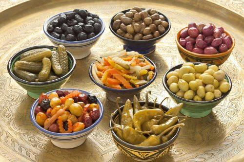 A decorated tray holds an assortment of small bowls, each holding a different preserved food such as olives, chili peppers, cornichons and marinated vegetables.