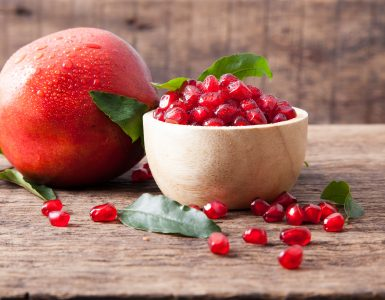 A small bowl full of juicy pomegranate seeds. A few seeds are scattered around the base of the bowl and a whole unopened pomegranate is in the background.