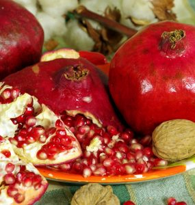 Image showing several wedges of pomegranate; the bright red seeds are exposed but still trapped in membrane. Several whole pomegranates are in the background. A single whole walnut rests beside a small pile of pomegranate seeds.