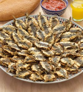 A large plate of fried sardines