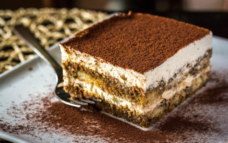 A square-shaped serving of tiramisu, an Italian dessert made by layering coffee-dipped ladyfingers with a mascarpone cream cheese mixture. The top of the dessert is heavily dusted with cocoa powder.