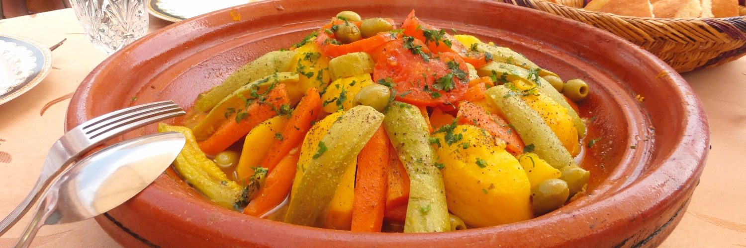 A close-up image of a Moroccan tagine. An assortment of vegetables including carrots, zucchini and potatoes are arranged in pyramid fashion. The dish is garnished with green olives and tomatoes.