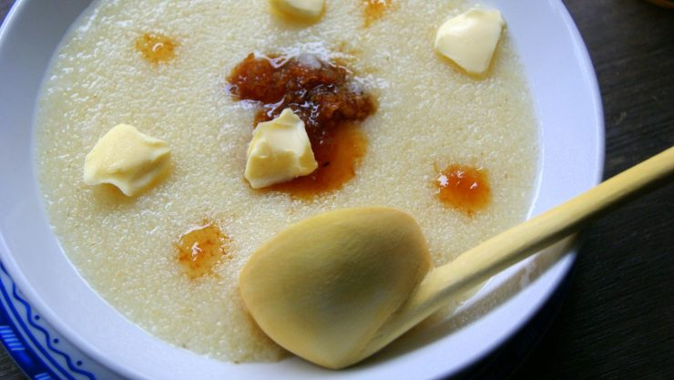 A deep plate filled with assida, a moroccan semolina porridge, dotted with butter and thick dark honey