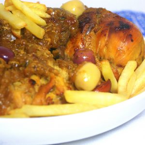 Moroccan chicken m'qualli with daghmira , fries and olives