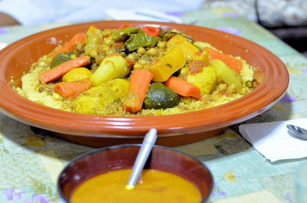 A large shallow ceramic dish called a gsaa is filled with couscous topped with meat and vegetables A bowl of broth is in the foreground.